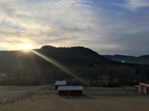 The sun is rising over the mountains and farm houses inside the Adirondack Park.